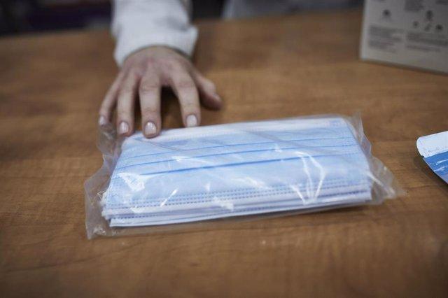 Una farmacéutica enseña a un cliente un paquete de mascarillas en la farmacia situada en la calle Tucán, 7, en el distrito de Carabanchel, Madrid (España), a 11 de noviembre de 2020. El Gobierno ha anunciado hoy que el Consejo de Ministros aprobará el mar