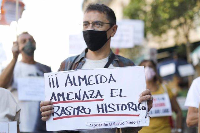 """El cofundador de Podemos y director del Instituto 25 de Mayo del partido morado, Juan Carlos Monedero, sostiene una pancarta donde se puede leer """"Almeida amenaza el Rastro Histórico""""."""