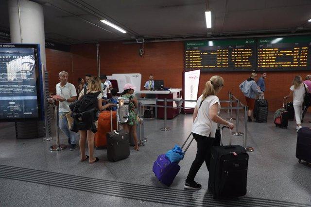 Varios pasajeros se aproximan a una oficina de venta de billetes de última hora en la estación de tren Puerta de Atocha de Madrid