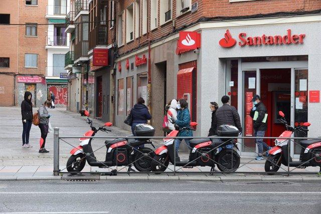 Varias personas esperan para entrar a una oficina del Banco Santander durante el inicio de la cuarta semana del estado de alarma decretado a consecuencia del coronavirus. En Madrid (España), a 6 de abril de 2020.
