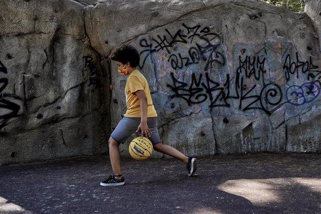 El niño actor y modelo Hugo Ndiaye, de 10 años, juega al baloncesto en un parque el primer día en el que los menores de 14 años de la Comunidad de Madrid pueden realizar paseos entre las 10 y las 13 horas y entre las 17 y las 21 horas, tras decidir la Com