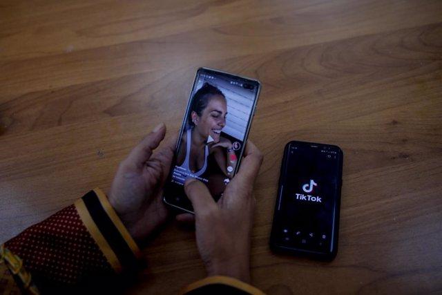Una persona mira en su móvil el vídeo de una joven en la red musical Tik Tok, en Madrid (España), a 22 de septiembre de 2020. TikTok ha publicado este martes su tercer Informe de Transparencia, que recoge la actividad del primer semestre de 2020, en el qu
