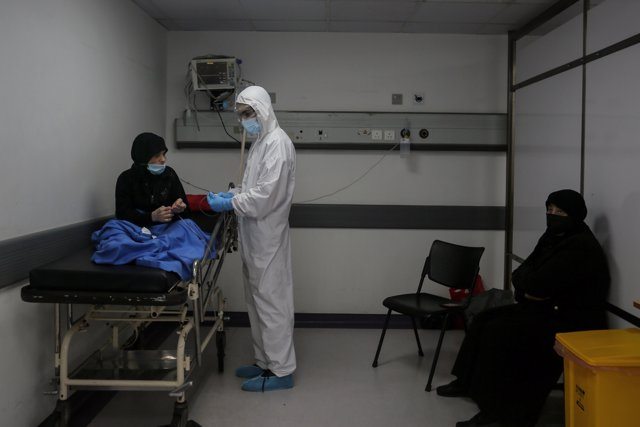 17 November 2020, Lebanon, Beirut: A medic wearing full protective gear checks a woman who might have contracted coronavirus inside an emergency room at the Rafic Hariri Hospital.