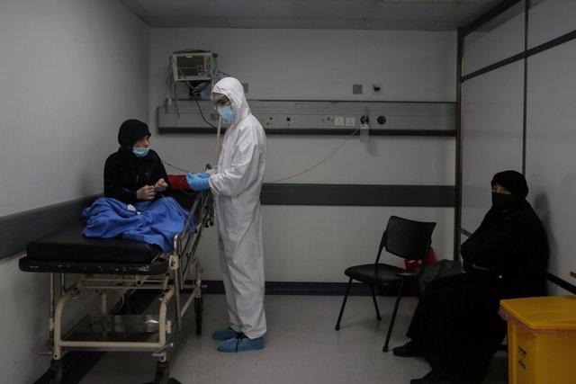 17 November 2020, Lebanon, Beirut: A medic wearing full protective gear checks a woman who might have contracted coronavirus inside an emergency room at the Rafic Hariri Hospital.