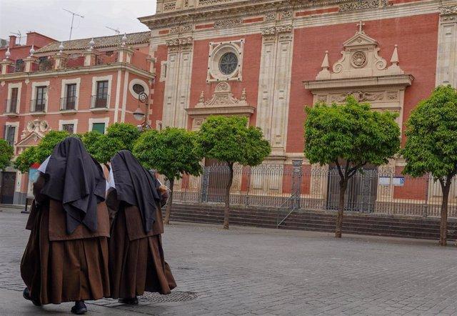 Dos monjas pasean por la plaza del Salvador. Sevilla.