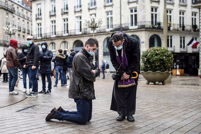 15 November 2020, France, Nantes: A Catholic priest listens to the confession of a believer during a gathering to call the reopening of places of worship as the national lockdown in France counties to stop the spread of the coronavirus. Photo: Sebastien S