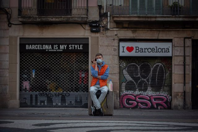 Un home escolta al seu telèfon mòbil enfront de dues botigues turístiques a Barcelona, Catalunya (Espanya), a 16 de novembre de 2020.