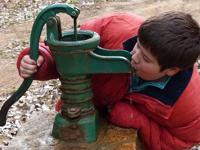 Niño bebe agua de una fuente.