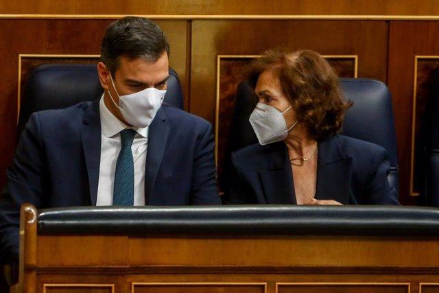 El presidente del Gobierno, Pedro Sánchez, habla con la vicepresidenta primera del Gobierno, Carmen Calvo, durante una sesión plenaria en el Congreso
