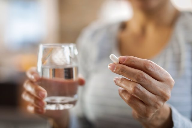 Female hands hold pill and glass of water