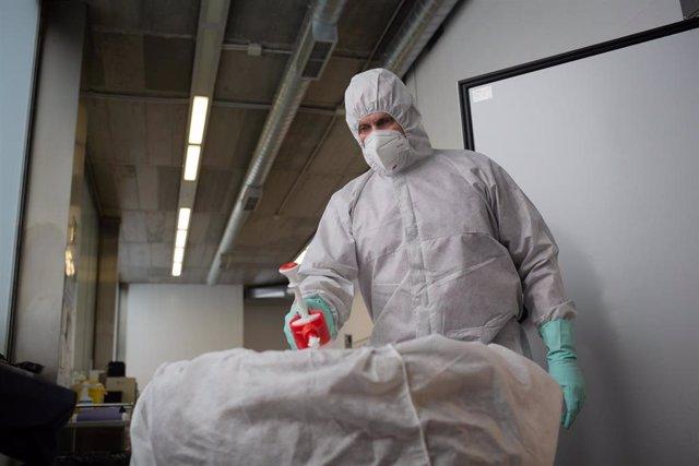 Un operario del Crematorio de Girona desinfecta el cuerpo de una persona fallecida con COVID-19 y su ataúd, antes de introducirle en el horno crematorio. En Girona, Cataluña, (España), a 6 de mayo de 2020.
