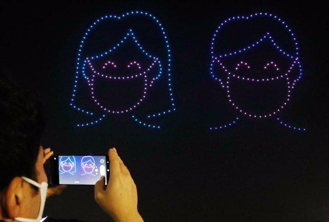 Drones dibujando con luces una pareja con mascarillas en Seúl