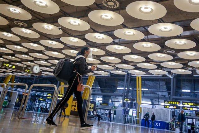Una pasajera camina por las instalaciones de la T4 del Aeropuerto Adolfo Suárez Madrid-Barajas, en Madrid, (España), a 12 de noviembre de 2020. En plena segunda ola de la pandemia del Covid-19, desde este jueves tal y como recoge el Boletín Oficial del Es