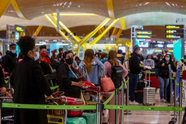 Filas de pasajeros esperan para dejar su maleta antes de embarcar en el avión en la T4 del Aeropuerto Adolfo Suárez Madrid-Barajas, en Madrid, (España), a 12 de noviembre de 2020.