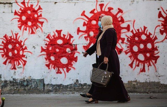 Mujeres junto a un mural sobre el coronavirus en el campamento de refugiados de Nuseirat, en la Franja de Gaza