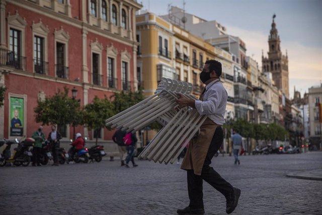 Un hostelero recoge el mobiliario de la terraza de un bar
