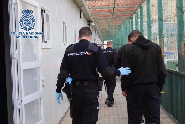 Un agente de Policía Nacional acompaña a un inmigrante en el CATE de Almería