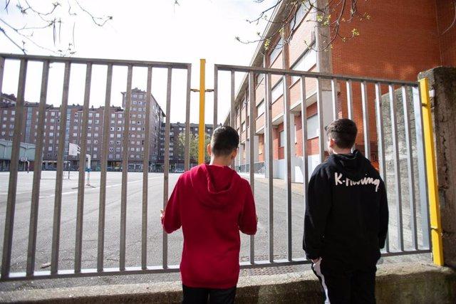 Dos adolescentes observan el patio cerrado de un colegio durante el confinamiento por el estado de alarma, cuando España es el único país que no deja a los menores salir a la calle y un día después de que la ministra de Educación anunciara que el curso es
