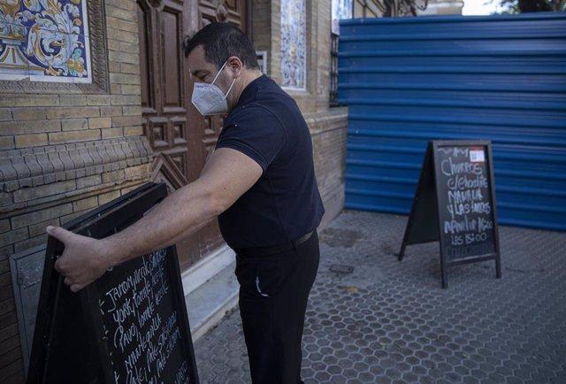 Un camarero quitando el cartel de su bar
