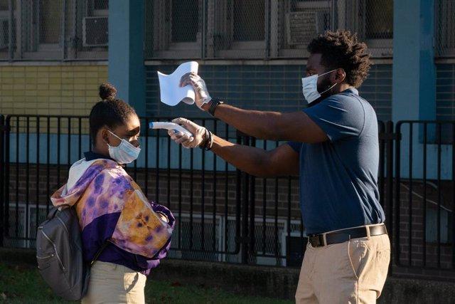 Un trabajador toma la temperatura a una niña antes de entrar en un colegio del Bronx, en Nueva York.