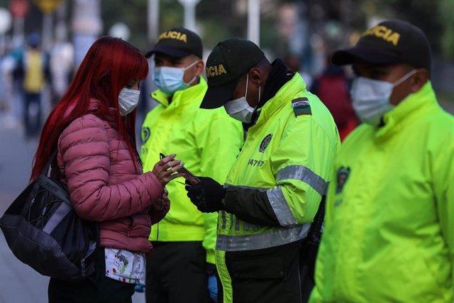 Agentes de la Policía revisando la documentación de una mujer en Colombia.