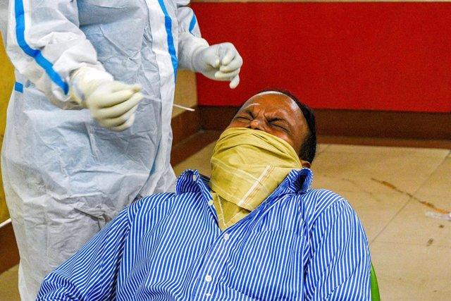 18 November 2020, India, Kolkata: A man cowers in discomfort during a swab test at a coronavirus (COVID-19) test center in Kolkata. Photo: Debarchan Chatterjee/ZUMA Wire/dpa