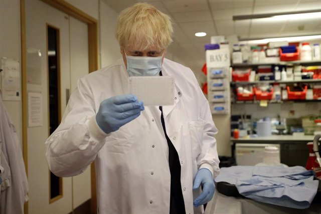 FILED - 18 September 2020, England, Oxford: UK Prime Minister Boris Johnson holds an immunological assay testing plate during his visit to Jenner Institute, where he meets with scientists who are leading the coronavirus (COVID-19) vaccine research.