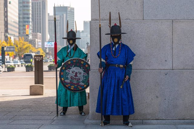 Dos guardias reales con mascarilla en la puerta principal del Palacio Gyeongbokgung, en Seúl