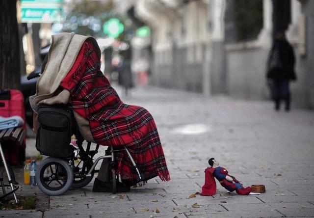 Una persona en silla de ruedas y tapada con una manta pide dinero en una calle de Madrid