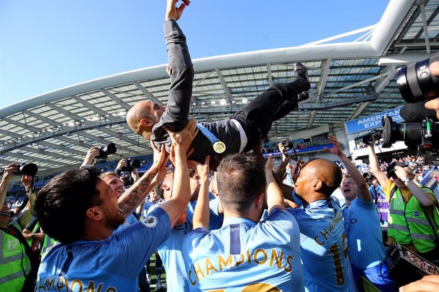 12 May 2019, England, Brighton: Manchester City manager Pep Guardiola is lifted up by his players whilst celebrating winning the title after the final whistle of the English Premier League soccer match between Brighton & Hove Albion and Manchester City at