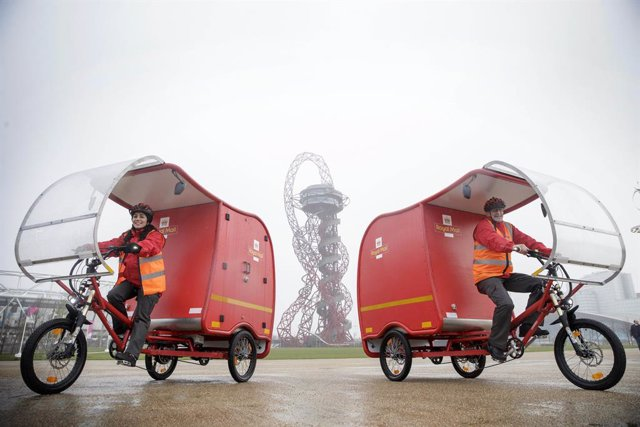 19 March 2019, England, London: Post people ride e-Trikes in front of the ArcelorMittal Orbit during the unveiling of the zero-carbon emission e-Trikes, which are predominantly powered by a combination of solar, battery and brake technology, and will be t