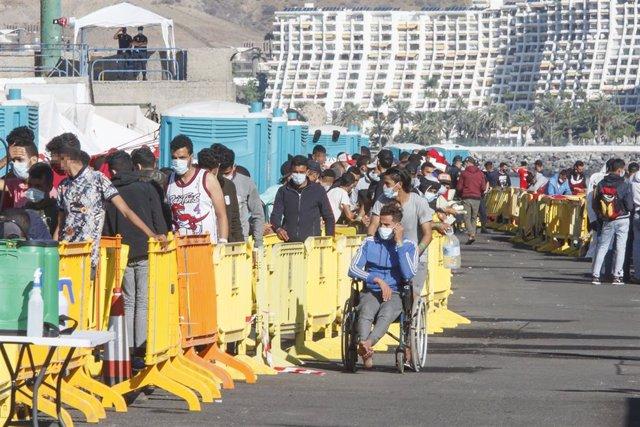 Varios inmigrantes hacen cola en el Muelle de Arguineguín, en Gran Canaria, Canarias (España).