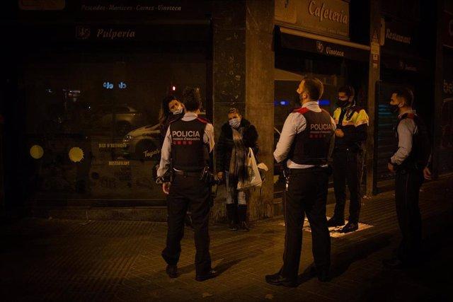 Varios Mossos d'Esquadra paran a una persona durante un control por el toque de queda impuesto a raíz de la crisis sanitaria del Covid-19 (Archivo)