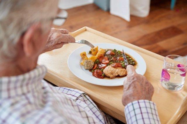 Over shoulder view of senior man eating dinner at home