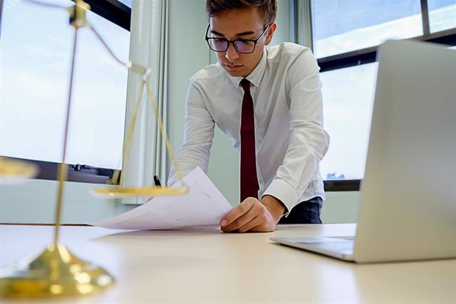 Trabajador del sector de la justicia con un ordenador en un despacho