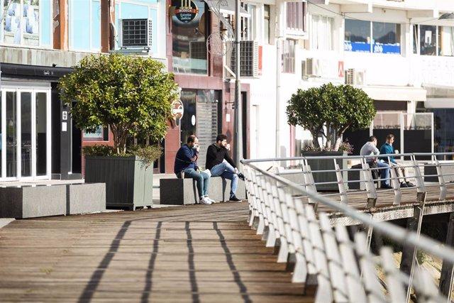 Dos personas permanecen sentadas en un banco de Sanxenxo, último municipio gallego en decretarse el máximo grado de restricciones