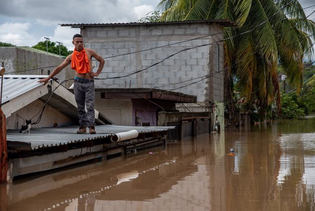 18 November 2020, Honduras, San Pedro Sula: Luis Omar waits on the roof of his flooded house to be rescued after the devastating hurricane Iota made landfall in Honduras. Photo: Seth Sidney Berry/SOPA Images via ZUMA Wire/dpa