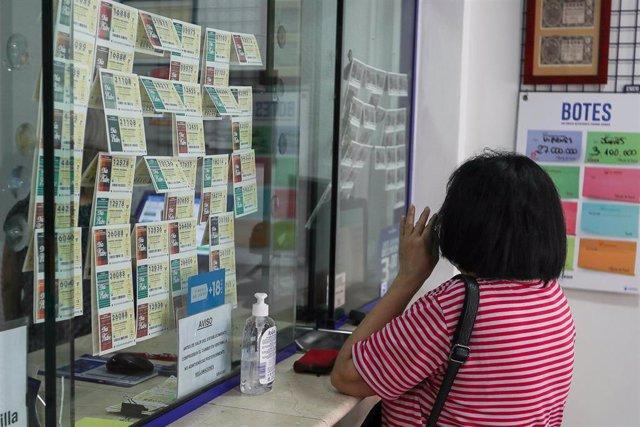 Una mujer compra lotería en una administración