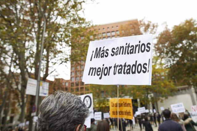 """Una persona sostiene una pancarta donde se lee """"'¡Más sanitarios mejor tratados!"""" durante una concentración de Enfermería de Madrid Unida, frente al Ministerio de Sanidad, en Madrid (España), a 15 de noviembre de 2020."""