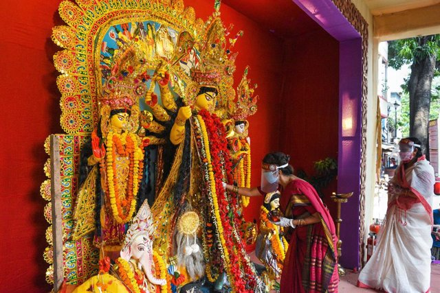 Mujeres con mascarilla hacen una ofrenda ante una escultura de la diosa Durga en Calcuta