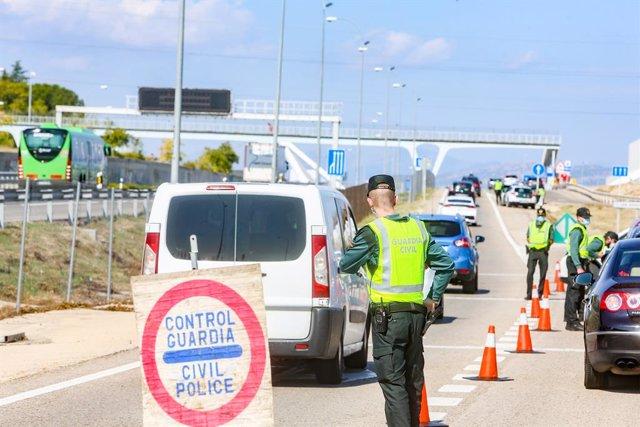 Agentes de la Guardia Civil vigilan durante un control efectuado en kilómetro 19 de la A-6, en Madrid, (España), a 10 de octubre de 2020. Este control, y otros realizados durante el día de hoy en la capital, se produce un día después de que el Consejo de