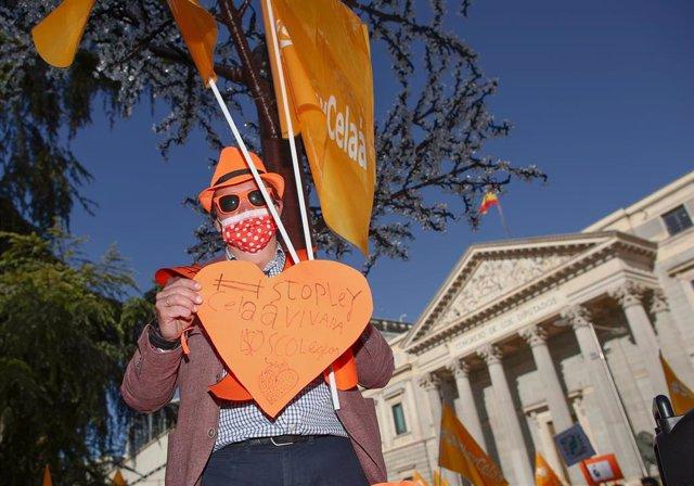 Un hombre sostiene una pancarta en una manifestación contra la Ley Celaá en el Congreso, el día de su aprobación, en Madrid (España), a 19 de noviembre de 2020. En esta manifestación han participado colectivos de la educación concertada y ha sido convocad