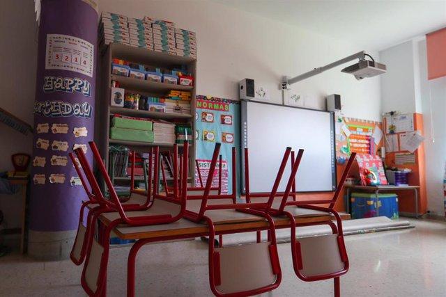 Mesas y sillas recogidas en un aula. Archivo.