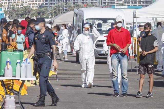 Un policia nacional, un sanitari i diversos immigrants a Arguineguín, a Gran Canària.