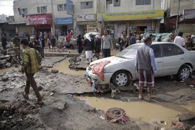 Un grupo de personas comprueba los daños causados por las inundaciones en la capital de Yemen, Saná