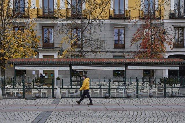 Una persona passeja al costat d'una mampara instal·lada en un restaurant de la Plaça d'Orient, a Madrid (Espanya), a 12 de novembre de 2020.