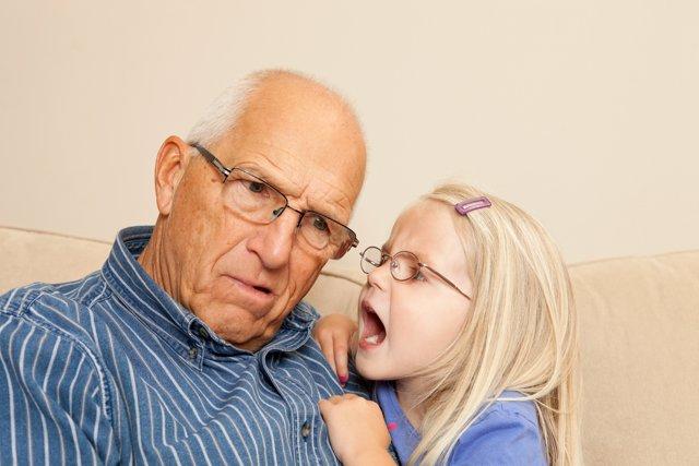 Niña hablando al oido de su abuelo sordo.