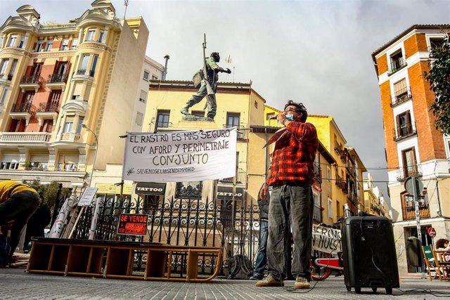 Varias personas sostienen carteles en una nueva manifestación de comerciantes de El Rastro.