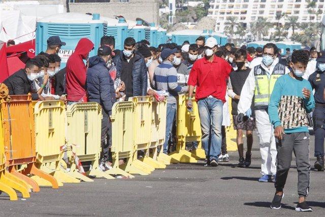 Varios inmigrantes hacen cola en el Muelle de Arguineguín, en Gran Canaria