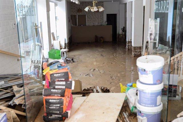 Interior de un local con el suelo lleno de barro tras la riada en Arganda del Rey por las lluvias.